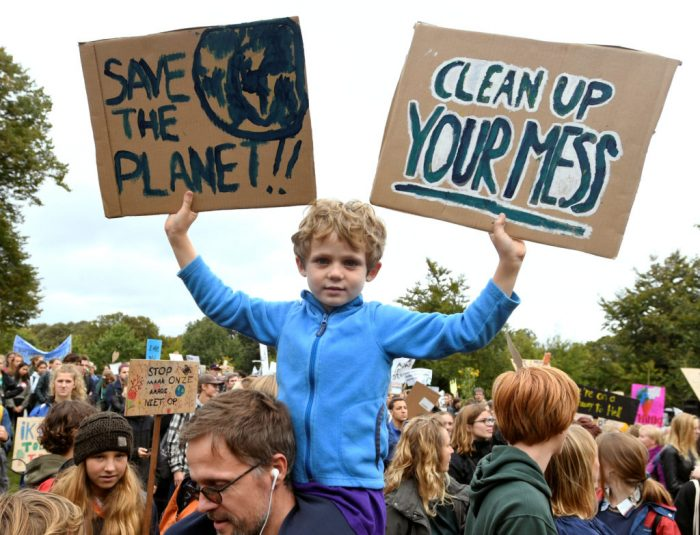 A child holds placards during a protest march to call for action against climate change, in The Hague, Netherlands September 27, 2019. REUTERS/Piroschka van de Wouw